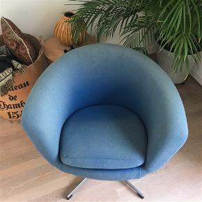 Stilfuld og elegant retro loungestol i blåt stof fra 1960erne. Loungestolen har en klassisk drejefod i stål, der sammen med det smukke tidsløse design, giver stolen et unikt og eksklusivt udtryk. Løs pude til sædet. Fremstår med originalt betræk - bleget af solen men intakt. Højde: 69 cm Bredde: 84 cm Dybde: 70 cm
