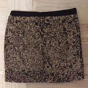 Fin nederdel med palietter - sort/guld. Str 2 - tænker det er S/M  Længde ca 38 cm - elastik i taljen.