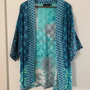 Sissel Edelbo kimono Model: Lotus short kimono  Størrelse: One size Købspris: 899,-  Smuk kimono fra Sissel Edelbo Super blød og utrolig lækker🌸💞  Skøn kort kimono fra Sissel Edelbo med brede ærmer. Kimono'en er lavet af 2nd hand silke mix fra en indisk sarie. Sarien er først vasket og derefter re-designed til denne skønne kimono. Kimonoen er helt unik. Den kan bruges løst eller med et bælte.  Kimonoen er lavet af genanvendte up-cycling vintage sarier. Alle sarier er håndplukkede af Sissel Edelbo, og er, før de blev re-designet, blevet båret af en indisk kvinde. Kvindens og sariens historie viser sig i de unikke mønstre og små karakteristika. Ved at bære denne smukke kimono fra Sissel Edelbo fortæller du historien videre.  Da stoffet er genanvendt, kender vi ikke den totale sammensætning af stoffet, som er håndplukket i Indien som en silke-mix. Der kan af samme grund forekomme små fejl, brugsspor el lign i stoffet. De små fejl er en del af sariens charme og historie og betragtes ikke som reklamation.  Alle produkter fra Sissel Edelbo er unikke.  Dvs der kun findes den ene du ser her på billedet, og kun i den viste størrelse.  Dét gør din kimono helt unik - og et smukt og farverigt alternativ til andre kimonoer.  LET THE STORY CONTINUE - FROM ONE WOMAN TO ANOTHER💞