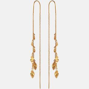 UNA EARLINE  Kædeøreringe af bølgede vedhæng med hammerslået overflade. Et organisk og orientalt udtryk som let kan styles med andre øreringe. Prisen er for et par.  Materiale: Sterling sølv (925) belagt med 18 karat guld i blankt poleret finish.