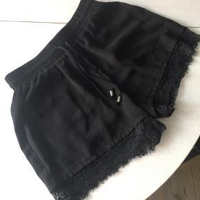 Sorte shorts med blondekant, meget behagelige at have på.
