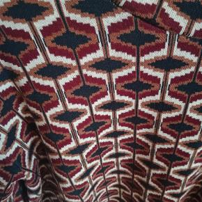 Mønstret bluse i hvide, røde, orange og sorte nuancer. 52 % viskose, 26 % bomuld og 22 % polyester. Køber betaler for evt. fragt.