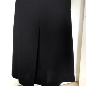 Knælang nederdel , dækker knæene. Læg for og bag, lommer i siden og lynlås bagpå.