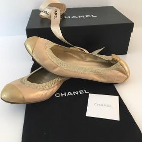 """Klassisk ballerina i str 38(C) fra Chanel med elastik i kanten, som giver en blød pasform (og ikke så """"stiv"""" i formen som de andre Chanel ballerinaer med grosgrain bånd i kanten).  Ballerinaerne er fra en cruise kollektion og således ikke en standardmodel, som produceres hvert år. Farven er guld med læder i rose gold.  Skoene er meget lidt brugt - dog er der en smule tegn på brug på sålen (såvel inder som ydersål.) De passer ikke min fod og må derfor videre.  Nyprisen i dag ligger Chanel ballerinaer (i lammeskind) ligger på over DKK 5.000.  Køber betaler porto og TS gebyr men jeg handler gerne via mobile pay."""