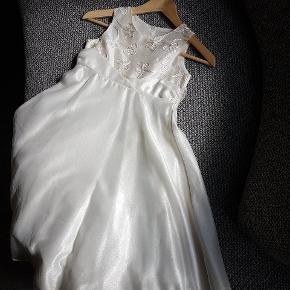 Råhvid creme farvet kjole som kun er brugt i 2 timer da min datter var brudepige. Den er renset efterfølgende. Er købt i Next i London. 2 størrelser 7 år højde 122cm hvoe kjolen er ca 89cm lang og str 9 år til 134cm høh pige hvor den er ca 100cm lang