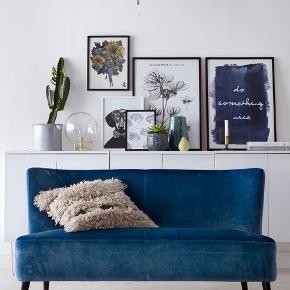 Blå Ellos Frederika sofa ca. 2 år gammel.  Stel af træ og betræk af blød polyesterfløjl. Polstring af polyether. Ben af gummitræ med detaljer af metal.   Mål: Højde 76 cm, bredde 140 cm, dybde 74 cm.  Siddehøjde 40 cm. Siddedybde 51 cm. Højde på ryg 43 cm.