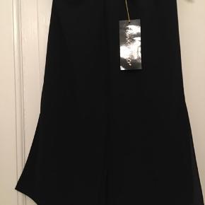 Elegant sort nederdel fra Frank Usher, str. 10, svarende til en medium. Nederdelen har lynlås og elastik i livet. Længde 65cm, slidser for, bag og i siderne giver ekstra vidde forneden. Aldrig brugt - stadig med mærke. 100kr Kan hentes Kbh V eller sendes for 38kr DAO