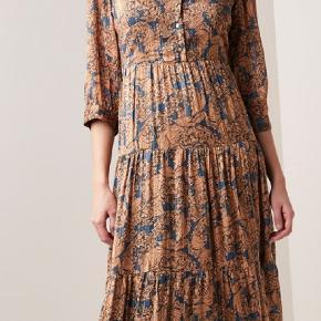 Super skøn maxi kjole med flot blomsterprint fra Lollys Laundry. Denne kjole har 3/4 ærmer med lidt puf effekt. Kjolen har knappelukning med små guld farvede knapper. Omkring taljen har kjolen en syning, som giver et fint og feminint look.