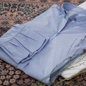 Smuk blå skjorte fra Mos Mosh med knapper i kraven og med bred løs kant forneden på ærmerne. Den er virkelig så flot. Str. S helt ny og med mærke på endnu, er i butikkerne nu. Kvalitet: 75% bomuld, 21% polymid, 4% elastan