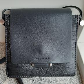 Flot læder taske med mønstret tryk i læderet. Brugt i 1 sæson og har derfor lidt små ridser i læderet, som ses på billederne. Ellers i god stand.  17x17x8 cm (str. som vist på billedet, samme taske model, men anden look)  Pris: 600kr. Eksl. Porto