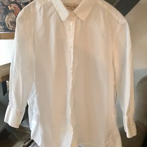 Lækker klassisk skjorte med et twist: peeplum bagpå og 3/4 ærmer. Alt i den skønneste, knitrende poplin. Brugt ganske lidt og vasket 2-3 gange. Brystmål 52 cm.