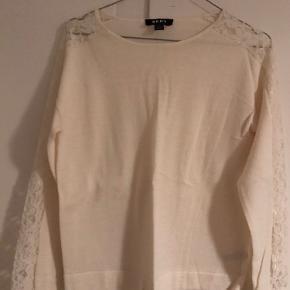 50 pct uld, 50 pct akryl. Med blonder på ærmerne