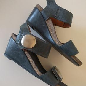 Super fine og meget skønne sandaler fra Cashott str. 38. Sandalerne er den kendte populære model med kilehæl. De sidder fantastisk på foden og de har en skøn pasform. De er i det skønneste bløde kvalitets skind og de er foret med et fint skindfor. De er brugt et par enkelte gange og de fremstår i rigtig pæn stand. Farven er koks grå med et tone af marineblå.