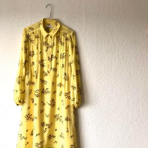 Smuk gul kjole med blomster. Går til knæene.
