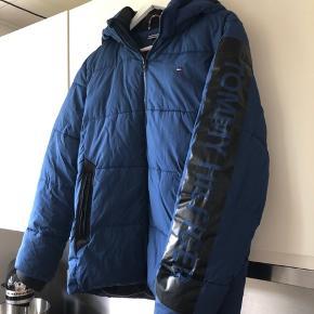 """Vinterjakke fra Tommy Hilfiger sælges, fa min søn ikke længere kan passe den. Den er størrelse 13-14 år, men min søn brugte den da han var 12 år og han er normal i størrelse. Den har været brugt som den """"pæne"""" jakke og der er derfor minimal slid på den, dog er der et lille mærke på hætten. Jeg har ikke gjort de store anstrengelser for at fjerne det, men det er heller ikke gået væk ved almindelig maskinvask. Køber betaler fragt, alternativt kan jakken hentes på min adresse."""