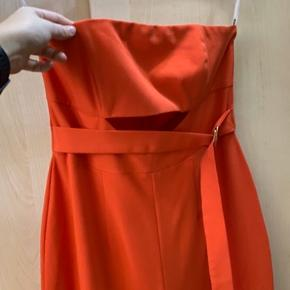 Helt ny lækker lakse/koral rød jumpsuit med lille udskæring under brystet og bælte.  Stor i størrelsen og ville derfor også kunne passes af en str 40.   OBS. køber betaler selv fragt 👍🏻
