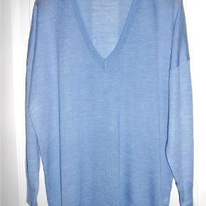 Oversize strikbluse i flot blå farve 52% uld/48% lyocell Brystmål 128 cm Længde 71 cm Aldrig brugt!