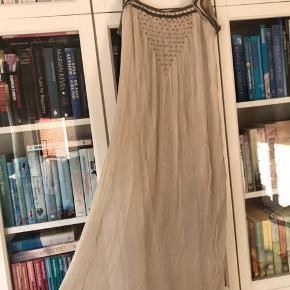 Smuk og enkel, lang kjole i tyverstil, men ned til læggen. Fin perlebesætning foran. Smuk med et bælte på. Der er et lille trådbroderi, som er gået lidt op. Man lægger ikke mærke til det, når den er på, men det skal nævnes, og har indflydelse på prisen😊