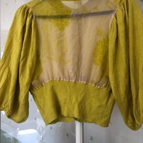 Flot kort cardigan med en flot gennemsigtig  ryg i 75 % silke
