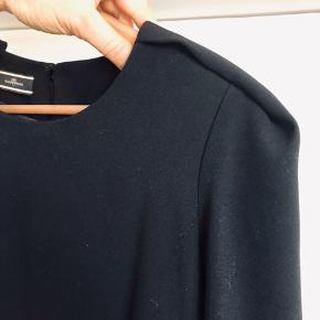 Smuk kjole i helt klassisk snit. Meget klædelig og med fin detalje ved skuldrene (se foto). Foret, så den glider glat.  Modellen hedder Zofir.