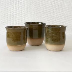 Tre skønne hånddrejede kopper af keramiker Knud Verner Knudsen. Kopperne er delvist glaserede i den smukkeste dybe grønne glasur, der giver en flot kontrast til den rå bund. Mål: Stor kop: Højde: 8,6 cm Diameter: 8,7 cm To mindre kopper: Højde: 8,5 cm Diameter: 7,5 cm