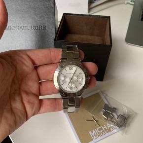 Michael kors ur modellen hedder MK 5932, det er aldrig brugt. Har fået taget et par led af, men det ligger i æsken, så de evt km sættes på igen, hvis uret skal forlænges.