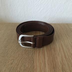 Sælger dette bælte i brun. Det er ikke ægte læder. Det måler 105 cm. Det er et smalt oh feminint bælte. Det har brugsspor (se billede). Pris sat herefter.