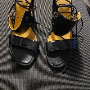 Smukke sandaler, hvor snorene kan bindes på flere måder, rundt om benet. Hælen er 10 cm. høj.