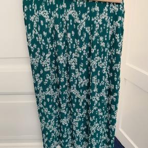 Rigtig fin plisseret nederdel. Grøn med hvide blomster. Svarer til en str. S