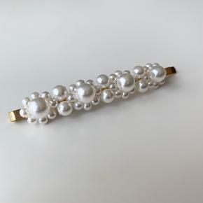 Ubrugt hårnål i guldfarvet metal med dekorative hvide perlemors perler.