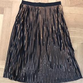 Plisseret nederdel med elastik i taljen. Str. M.