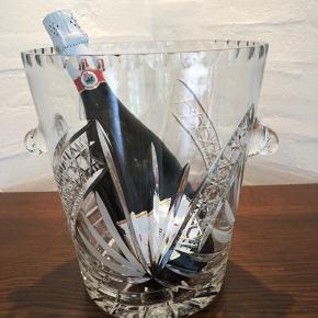 Den mest fantastiske og store champagnekøler i krystal. Her er tale om det ypperste, når du vil servere kølig champagne, vin eller lignende.  Denne køler er noget af det smukkeste jeg nogensinde har set. Den har de flotteste slibninger og er udført i den smukkeste mundblæste kvalitet.  I topstand og uden skader og skår.  Højde 25cm Ø 22cm Til info sælges lignende champagnekølere i krystal til minimum 2000 kr.