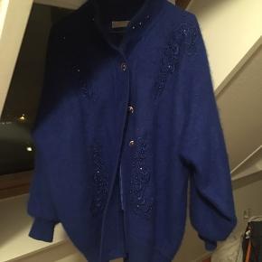 Super smuk og blød blå cardigan med lidt skulderpuder. Yderside: 80 % Angora, 10 % uld og 10 % akryl. For: 100 % akryl.