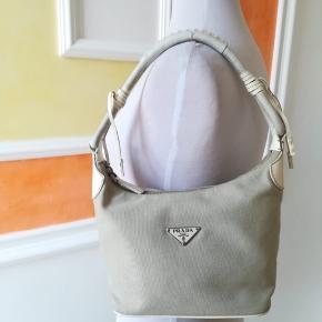 🔥🌟👜Prada, medium taske i beige stof og hvid lædertaske. 👜👜  Hånd eller underarm Prada vintage stof, beige og hvid farve. Åbning med lynlås. Ingen tydelige tegn på slid. Det eneste rum med lynlås og indvendig lomme. Gode vinkler. Der er små revner på håndtaget. Målinger cm 20x10x15. Skulderrem 18 cm. Uden støvpose.  Vi er til rådighed for flere billeder.  Bemærk venligst, at det er en vintage produkt, der anvendes, af denne grund tegn på brug kan være til stede. Meget god stand