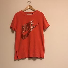 Flot koralfarvet Nike t-shirt i str. S.  Brugt en gang er derfor i rigtig god stand.  Kan afhentes i Ørestad eller sendes.