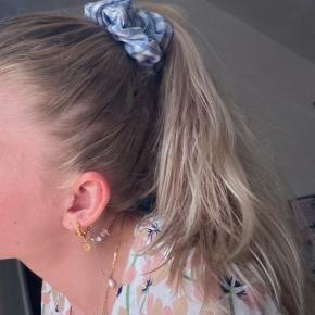 Scrunchie med god og stram elastik, fås i både lyserøde og blå tern Byd gerne