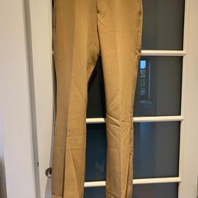 """Neo Noir Cassie bukser i farven Camel.   En smule """"fnuller"""" på venstre lår, hvilket ses på det ene billede.  OBS! De har lagt i et skab længe, derfor de er en smule krøllet"""
