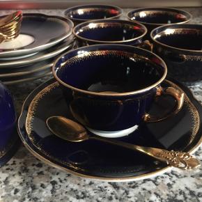 Mokka- / espressokopper med guldskeer - måske antik (arvestykke)   6 kopper med underkopper i porcelæn / China fra Chodziez Made in Poland Meget mørkeblå farve med guldkant, guldbort og hank på kopperne Underkop Ø 12,5 cm Kop Ø 7 cm højde ca. 4 cm  9 guldfarvede teskeer stemplet med MEKA Hver teske måler 9,5 x 2 cm  Ingen skår eller skader Kun afhentning