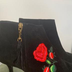 Skoene er i en skøn ruskind med blomster broderi på siden samt lynlås Skoene er aldrig brugt som det også ses på sålen  Hælen måler 7,5 cm