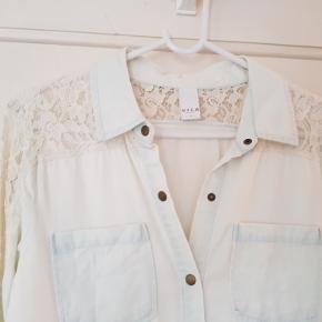 Lækker lys denimskjorte med blondekant på skulder og ærmer Trykknaplukning og to brystlommer. 63% bomuld/37% tencel. Brugt 1 gang, så er som ny.  Mål Længde:  72cm Bryst: 50cm  Talje: 47cm Bundkant: 51cm