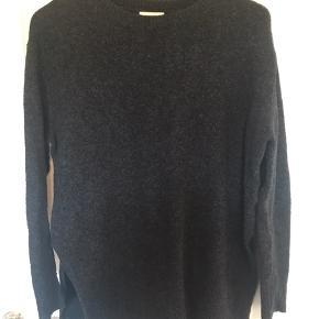 Flot mørkegrå sweater. Høj slids i siden. Brugt men rigtig fin stadig.  Ved køb af flere ting kan der fåes rabat. Sender gerne på købers regning