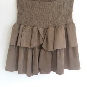 Fin Neo Noir nederdel i ruskindslook. Modellen hedder Carin skirt seude. 90% polyester, 10% elastane.   Den er i pæn stand, men tråden er gået et par steder i ribkanten. Man ligger mest mærke til det hvis den er stærkt helt ud. Se billede 3.
