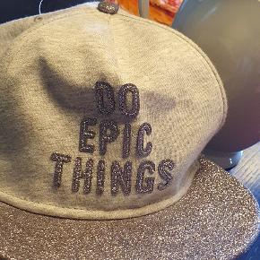 En meget fin kasket, til piger:) på skyggen, er der sølv glitter. Der er skrevet med glitter  DO EPIC THINGS.