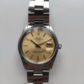 Rolex Oyster Perpetual Date fra 1983 i stål med skive af guld.  Ref 15053, som også fremgår af certifikatet på uret. Uret kommer alene som ur, dog medfølger en rød vintage Rolex æske fra et andet ur.  Uret er registreret i Watch-matters, og blev tryktestet forud for registreringen, samt serviceret inden køb tilbage i februar 2020.