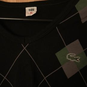 Sælger denne lacoste t-shirt i sort med grøn og grå tern den fejler intet det er en str. XL men svare til en S/M byd gerne