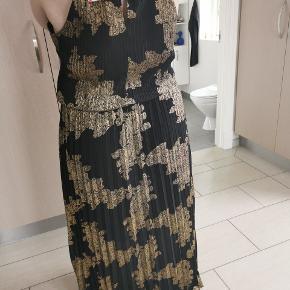 Flot og feminin lang kjole  Kjolen har fin lukning ved hals og er uden ærmer. Den har underkjole Svarer til 46/48