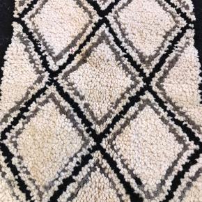 Lille håndknyttet uldtæppe med berbersymboler i nordiske farver. Måler 80x53 cm