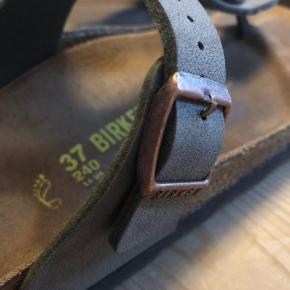 Den klassiske sandal fra Birkenstock.  Der er synlige fodmærker, som også ses på billedet. Men sandalen er faktisk brugt ganske lidt. Det ser man også på remmen og sålerne, der fremstår som nye.
