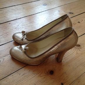 Varetype: Smukke skind heels med lille sløjfe Størrelse: 39/5 (39) Farve: guld Oprindelig købspris: 2600 kr.  Brugt få gange - fremstår som næsten nye.  Super fine til jeans eller til fest, jul og nytår.  Str 39,5 men jeg er str 39 og passer dem.  Mål: Indvendig længde: ca 26,5 cm Udvendig hælhøjde: ca 10,5 cm Indvendig hælhøjde: ca 7,5 cm  Æske og dustbags medfølger.  Bytter ikke   *** se også mine andre annoncer med mærkevarer ***