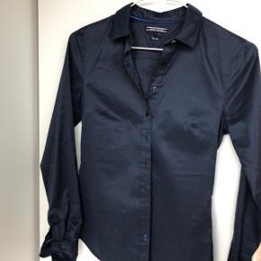 Mørkeblå skjorte fra Tommy Hilfiger i slim fit købt i USA (derfor står der str. 2 på mærket). Kun brugt et par gange, da den var for lidt for lille.